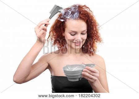 Young beautiful woman dyeing hair on white background