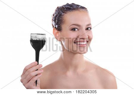Young beautiful woman holding brush with hair dye on white background