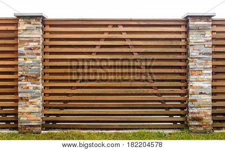 Wooden Garden Fence With Stone Paved Pillars Guarding Private Property.