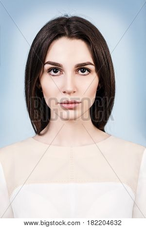 Portrait of young beautiful woman over blue background