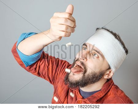 Man In Medical Bandage Holding Pills In A Hand