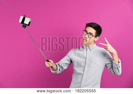 Young Asian man taking selfie on color background