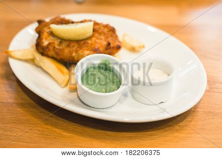 Mashed Peas And Sauce On Plate With Fish And Chips.