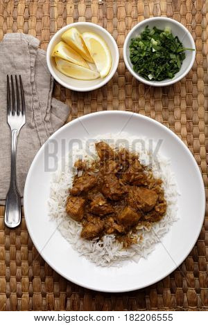 Chicken curry with rice, lemon, and greens