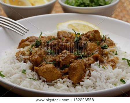 Chicken curry with rice, lemon, and parsley