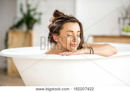 Beautiful young woman relaxing lying in the bathtube in the bathroom