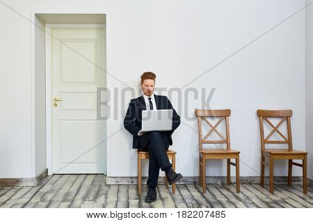 Portrait of confident young businessman using laptop in waiting room outside office