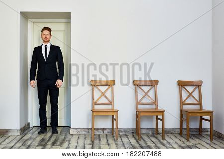 Portrait of confident young red haired  businessman standing by door in waiting room, leaving office