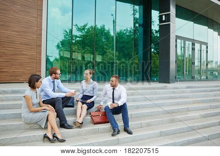 Group of young business people sitting on steps outside modern office building with glass fronts discussing work