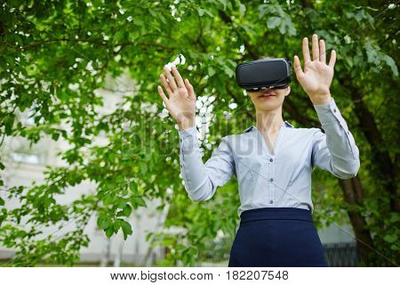 Portrait of female office worker wearing VR glasses experiencing forest and sounds of nature to relieve stress
