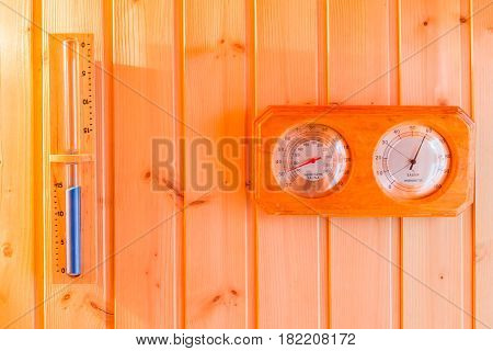 Bath thermometer hourglass decorated on interior wooden wall of private sauna room.