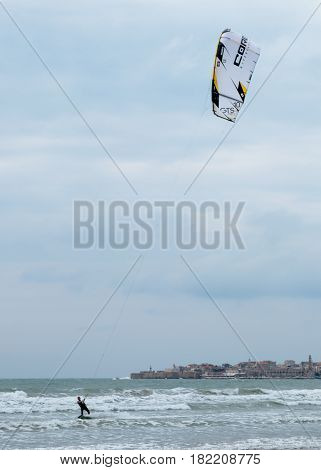 Acre Israel - April 15 2017 : Young man in a dark waterproof suit is engaged in kiteboarding in windy weather on the Mediterranean Sea near Ako Israel