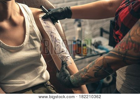 Female master making design of tattoo image on hand of woman in salon