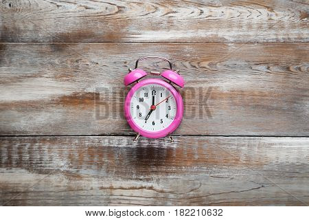 Pink Alarm Clock On Brown Wooden Table