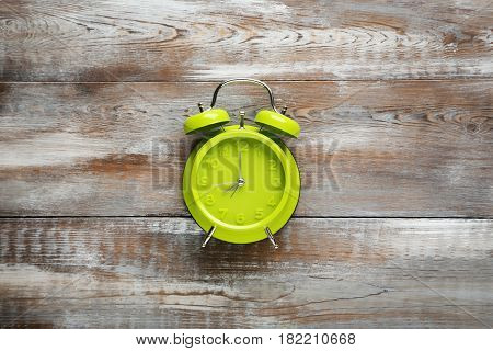Green Alarm Clock On Brown Wooden Table