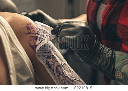 Close up temporary tattoo on arm of client which making worker in gloves