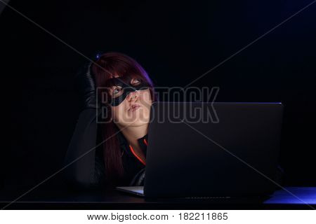 Young woman hacker with laptop