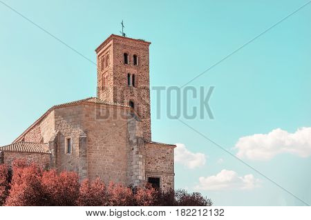The church of Santa Maria del Castillo in Buitrago de Lozoya in Spain, against a teal blue sky with a place for text