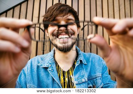 Funny smiling guy with glasses for sight. He holds glasses in his hands and smiles strongly with his teeth. The concept of excellent vision.