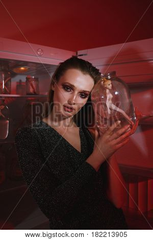 Image of serious young woman standing at night near refrigerator holding bottle with doll. Looking at camera.
