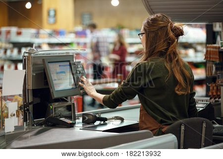 Back view photo of cashier woman on workspace in supermarket shop. Looking aside.