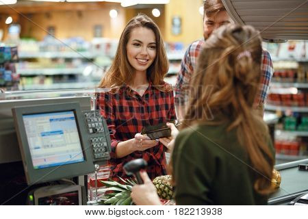 Picture of cheerful young loving couple standing in supermarket shop near cashier's desk. Looking aside.