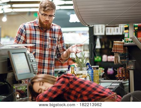 Picture of confused man looking at sleeping cashier lady on workspace in supermarket shop.