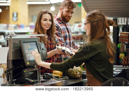 Photo of happy young loving couple standing in supermarket shop near cashier's desk. Looking aside.
