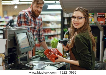 Picture of happy cashier woman on workspace in supermarket shop. Looking at camera.