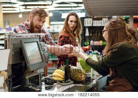 Image of angry young man standing in supermarket shop near cashier's desk doesn't give the credit card to cashier. Looking aside.