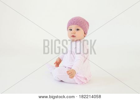 Photo of cute little baby girl wearing hat sitting on floor isolated over white background. Looking at camera.