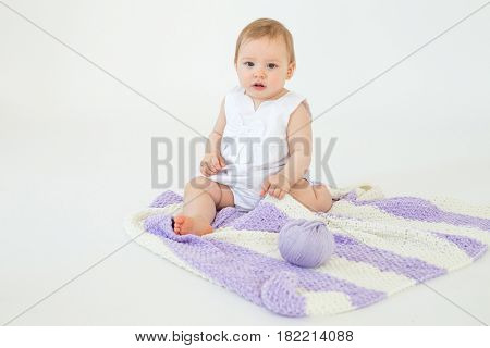 Photo of cute little baby girl sitting on floor with plaid isolated over white background. Looking at camera.