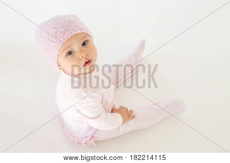 Photo of cute little baby sitting on floor over white background. Looking at camera.