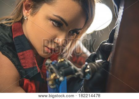 Focus on face of female tattoo master expressing attention concentration. She making image with special technical device. Portrait