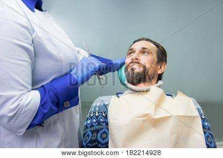 Dentist and patient. Mature man looking at doctor. Consult a professional.