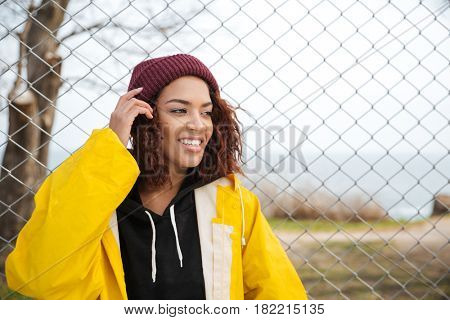Photo of cheerful african young lady walking outdoors dressed in yellow raincoat. Looking aside.