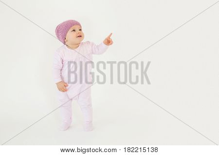 Photo of cute little baby girl wearing hat standing on floor isolated over white background. Looking aside and pointing.