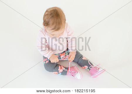 Photo of cute little baby girl sitting on floor isolated over white background. Looking aside.