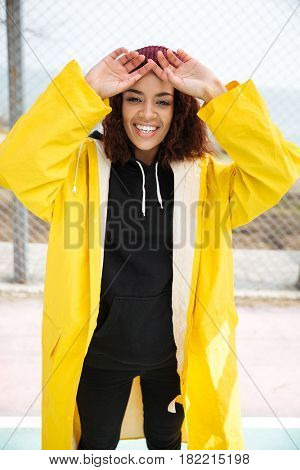 Image of cheerful african young lady walking outdoors dressed in yellow raincoat. Looking at camera.