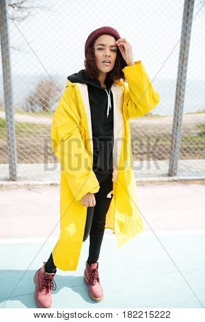 Picture of serious african young lady walking outdoors dressed in yellow raincoat. Looking at camera.