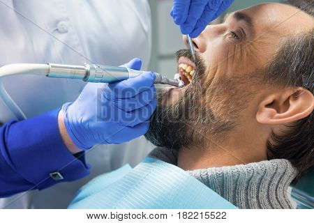 Dentist cleaning teeth. Hands of stomatologist with tools. Dental health services.