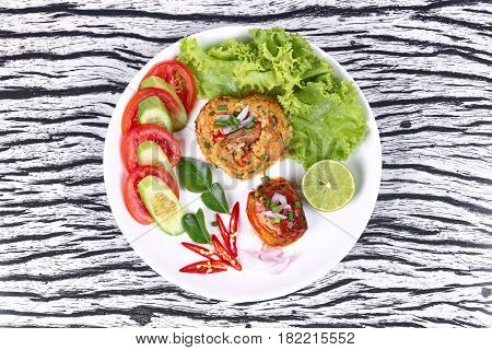 Thai food Fried jasmine rice with canned fishmackerel in tomato sauce topped halve green lemonsliced tomatocucumberred chilired onionlettuce and kaffir lime leaves.