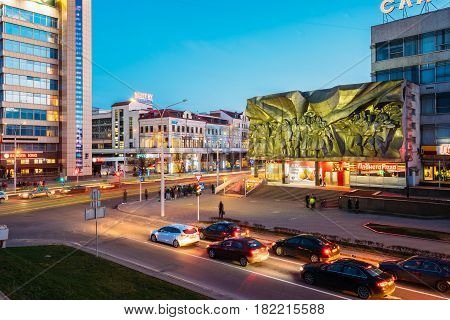 Minsk, Belarus - April 3, 2017: Evening Night Traffic Near Bas-relief of the Soviet era on old facade building On Illuminated Nemiga Street In Minsk, Belarus