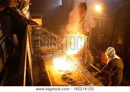 Splashes of molten metal at the plant. Blast furnace which melts metal ore.