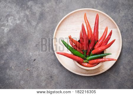 red chili or red hot chili peppers on wood bowl
