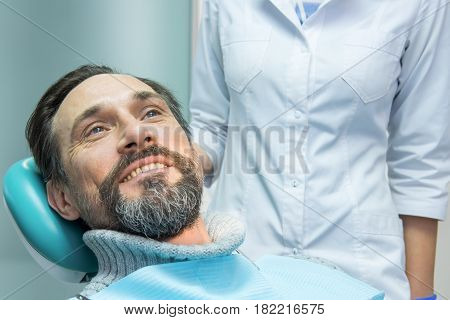 Mature male at the dentist. Patient of stomatologist. Health insurance tips.