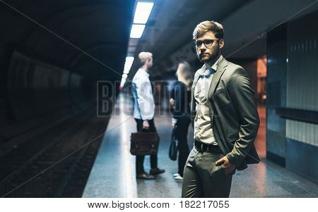 Young business people waiting for transportation underground
