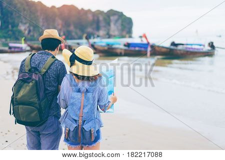 Young love couple traveler with backpack and hat looking map at the sea with long boat thailand background from Ao Nang Beach Krabi. Traveling in Krabi Thailand Traveler summer concept