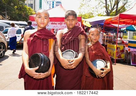 YANGON, MYANMAR-MARCH 3, 2017: Three unidentified young novice monks walking morning alms in Yangon, Myanmar on March 3, 2017.