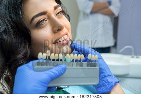Patient and tooth color chart. Young woman smiling. Effective teeth whitening.
